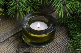 Photo of small candle in glass votive and evergreen branch.