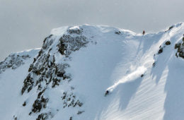 photo of backcountry skier on mountain peak from a distance.