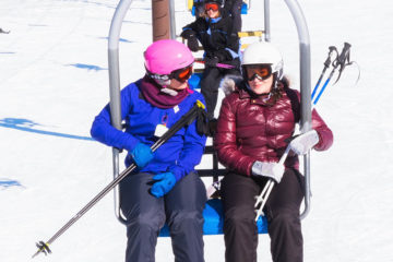 Photo of two female skiers riding the chairlift.