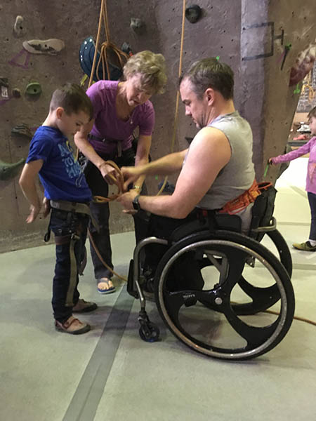 Photo of Tyler Byers in wheelchair, tying a figure-eight through his son's harness.