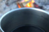 Photo of a camp mug in front of a fire.