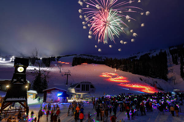 Photo of crowd looking at fireworks over ski hill.