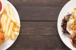 Photo of plate of chicken and fries versus plate of salad.