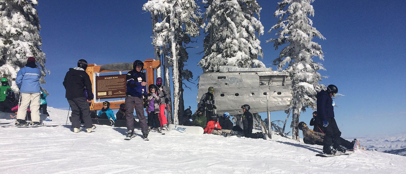 Photo of skiers and boarders standing in front of the bomber's wing and a plaque on Mission Ridge.