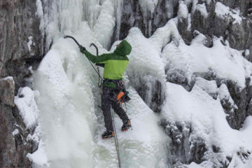 Photo of ice climber assessing route.