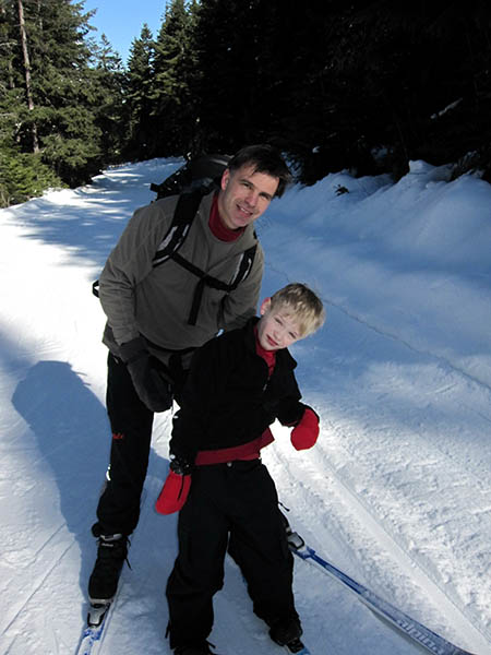 Photo of Trevin Hansen on nordic skis being supported by his father.