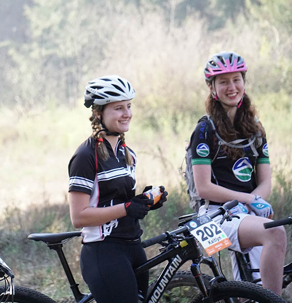 Photo of two girls by their bikes with race bibs.