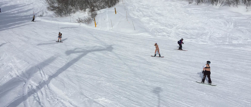 Photo of skiers wearing swimwear on the slopes.