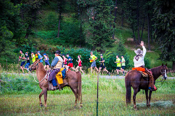 Photo of volunteers on horseback cheering on runners.