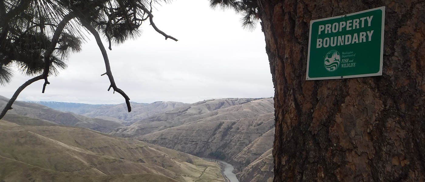 Close up view of the property boundary sign on a tree and the Grande Ronde River in the background.