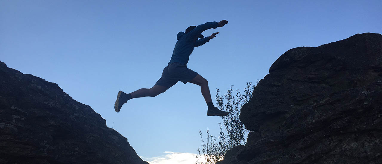 Silhouette of man leaping from one boulder to the next.