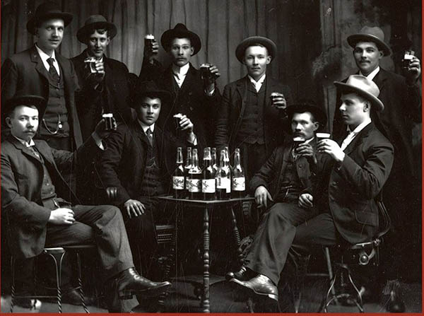 Historic photo of men sitting around a table with bottles of alcohol.