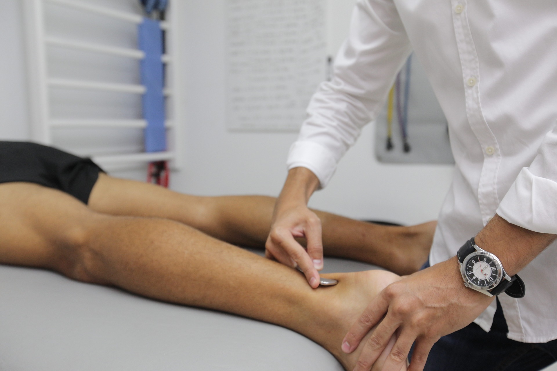 Close up of physical therapist pressing on patient's ankle.