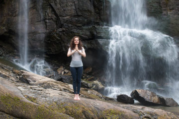 Photo of person practicing yoga in front of waterfall.