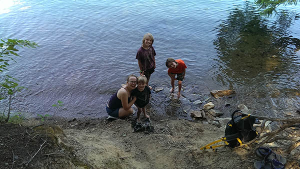 Children cooling off in Sullivan Lake with feet in the water.