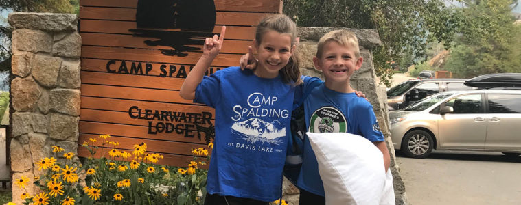 Photo of siblings in front of Camp Spalding sign