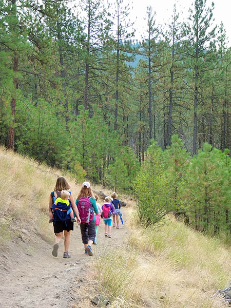 Photo of kids and parents hiking along single track hiking trail.
