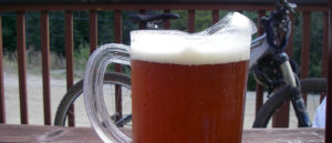 Photo of beer on picnic table with bike in the background leaning against deck railing.