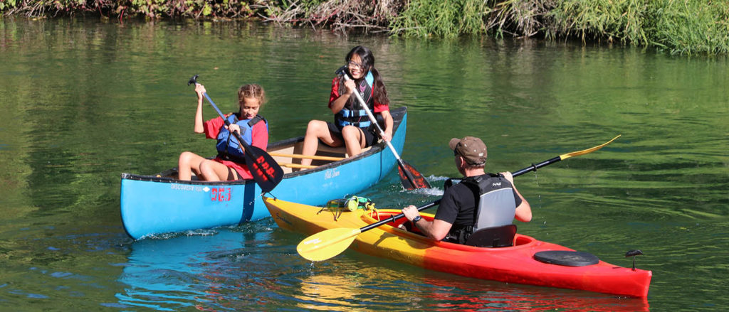 Two teenage girls paddling a blue canoe and a man paddling a red and yellow kayak on the Little Spokane River at Saint George's School.