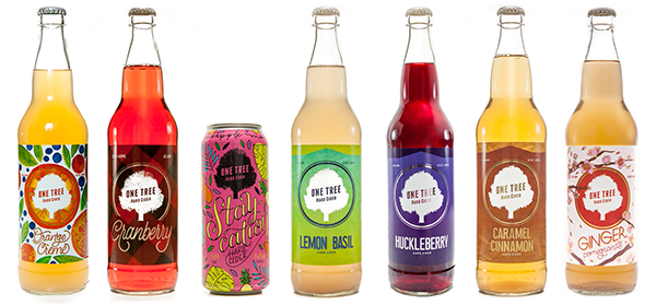 Line of 6 hard cider bottles, and one can, of all the different flavors of hard ciders made by One Tree Hill.