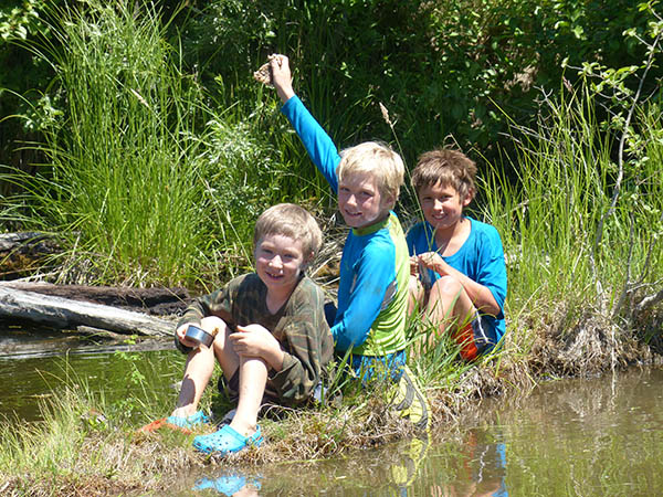 Photo of three boys sitting on a river bank.