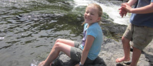 Photo of girl sitting on a rock with her feet in the water.