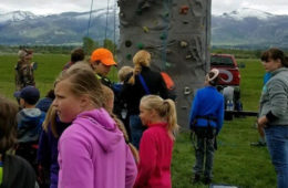 Photo of kids standing around a fiberglass rock wall.