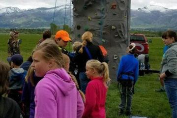 Photo of kids standing around a fiberglass rock wall.