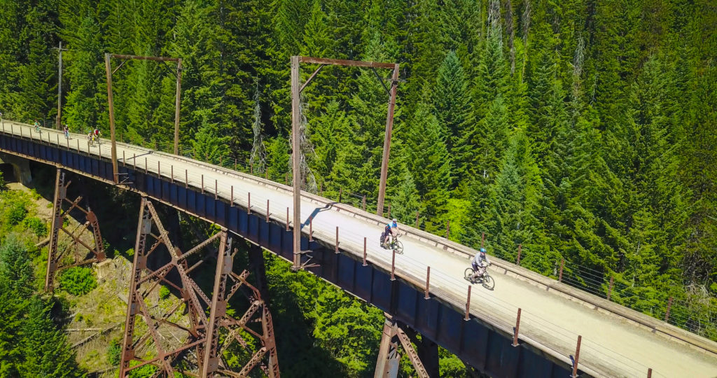 Bikers pedaling along a high trestle bridge on the Route the Hiawatha in North Idaho.