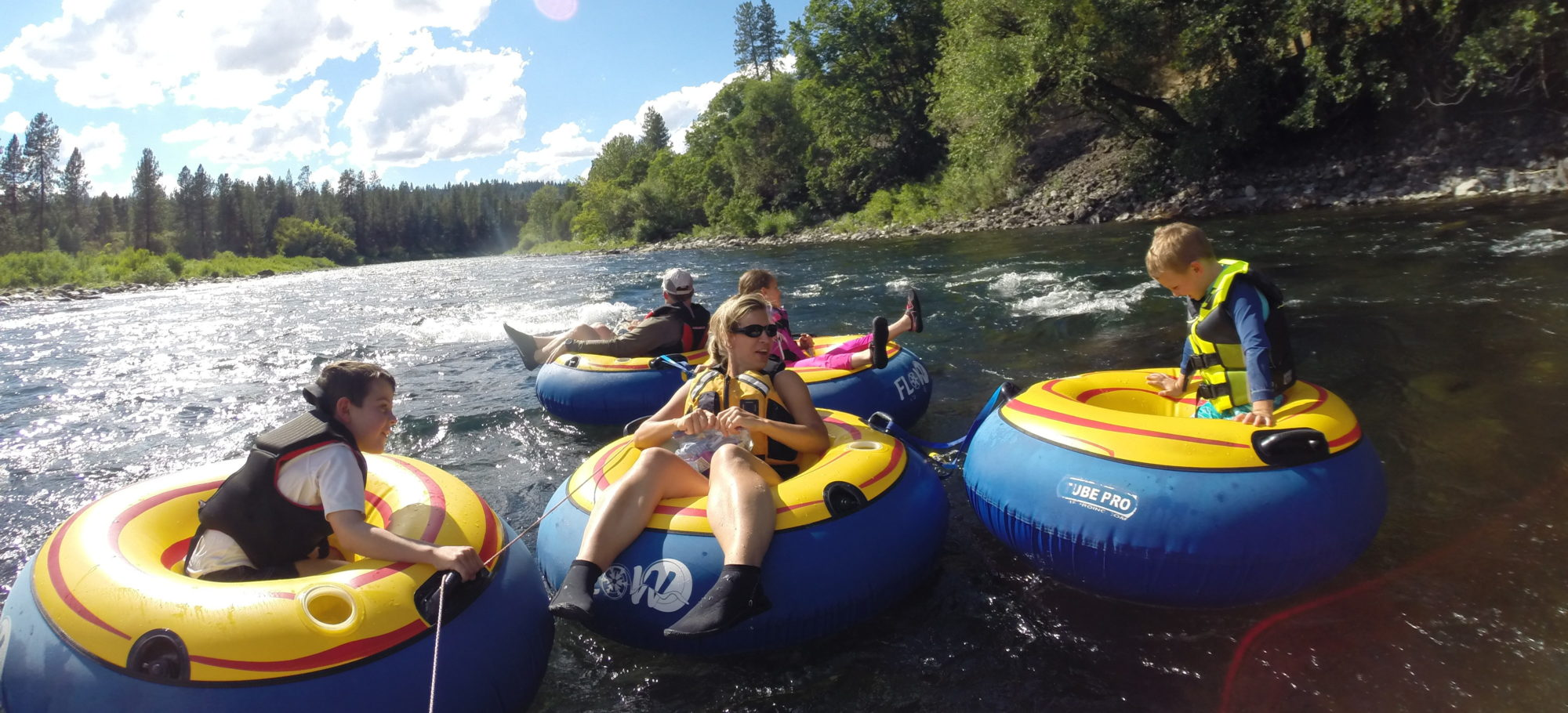 Mom, dad, and children tubing on the Spokane River, using big blue and yellow inflatable tube rentals from FLOW Adventures. Small whitewater rapids on the water and trees along the riverbank.