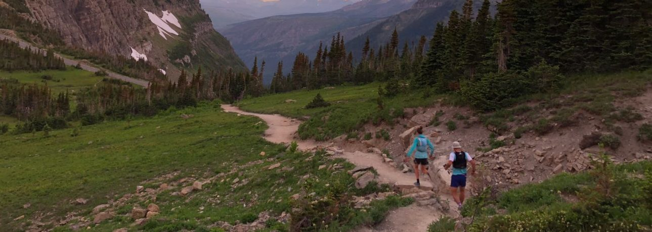 Runner along a singletrack dirt trail in the backcountry, through a meadow, with mountain peaks in the distance.