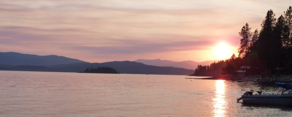 Sunset at Lake Pend Oreille, with rich hues of pink, yellow, and orange in the sky.