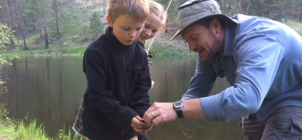 Father helping his children with a fishing hook and line at the river.