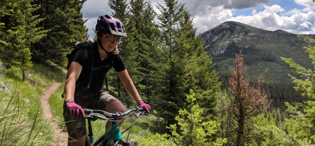 Woman mountain biking on a dirt trail with a view of trees and mountain peaks in the background.