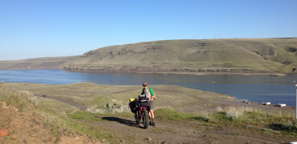 Man standing alongside his bike on the Columbia Plateau Trail State Park aside the Snake River in southeast Washington.