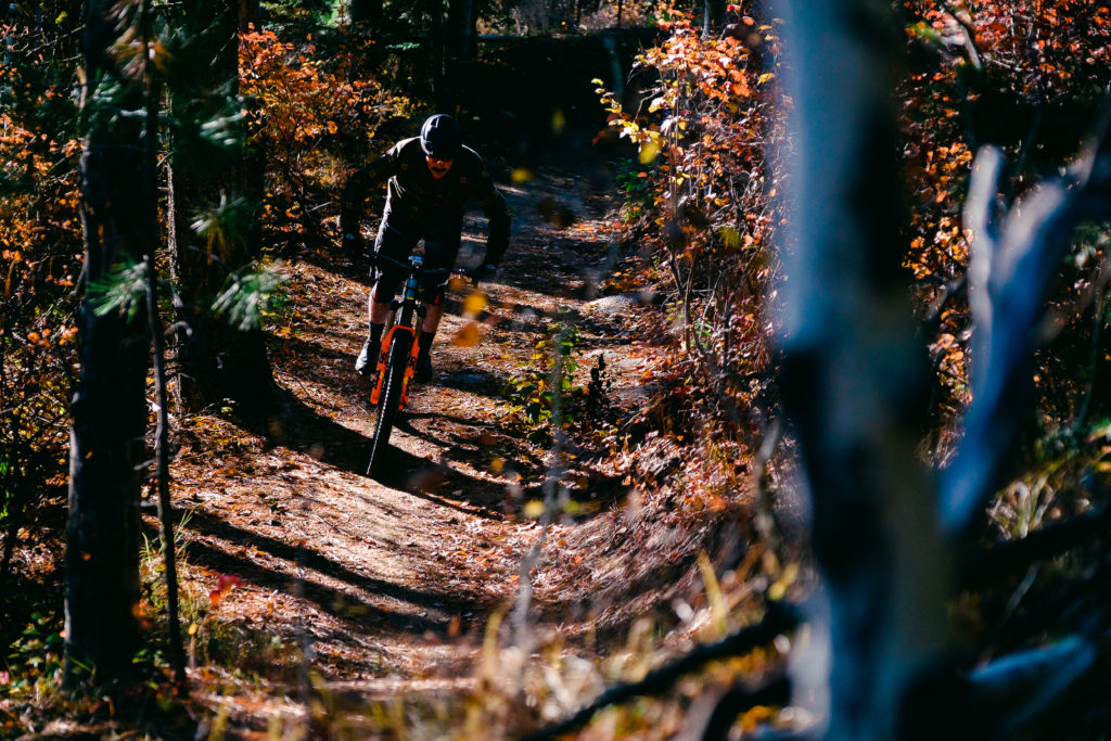Mountain biker riding down a dirt singletrack with fall-colored trees alongside the trail.