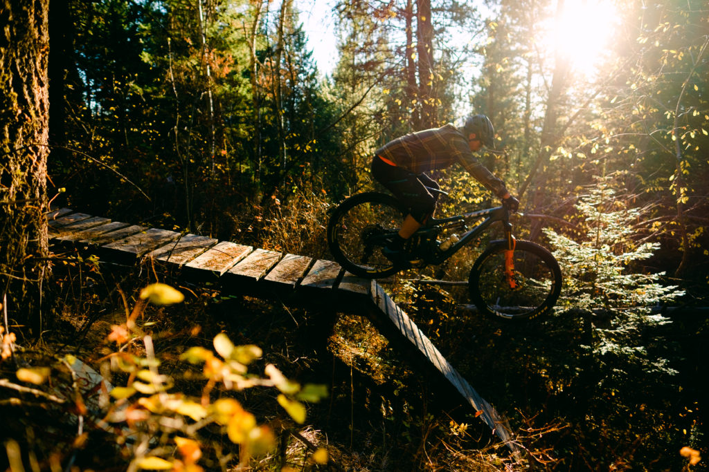 Mountain biker riding over a wooden bridge on a singletrack trail.