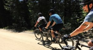 People riding gravel bikes on a dirt road.