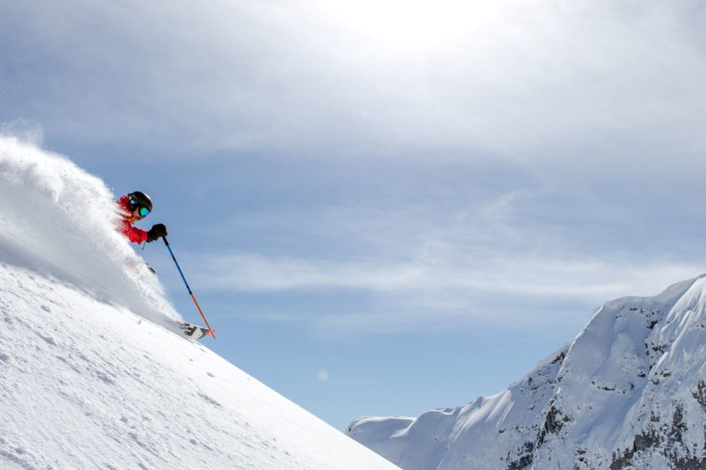Skier going down a steep and deep powder run