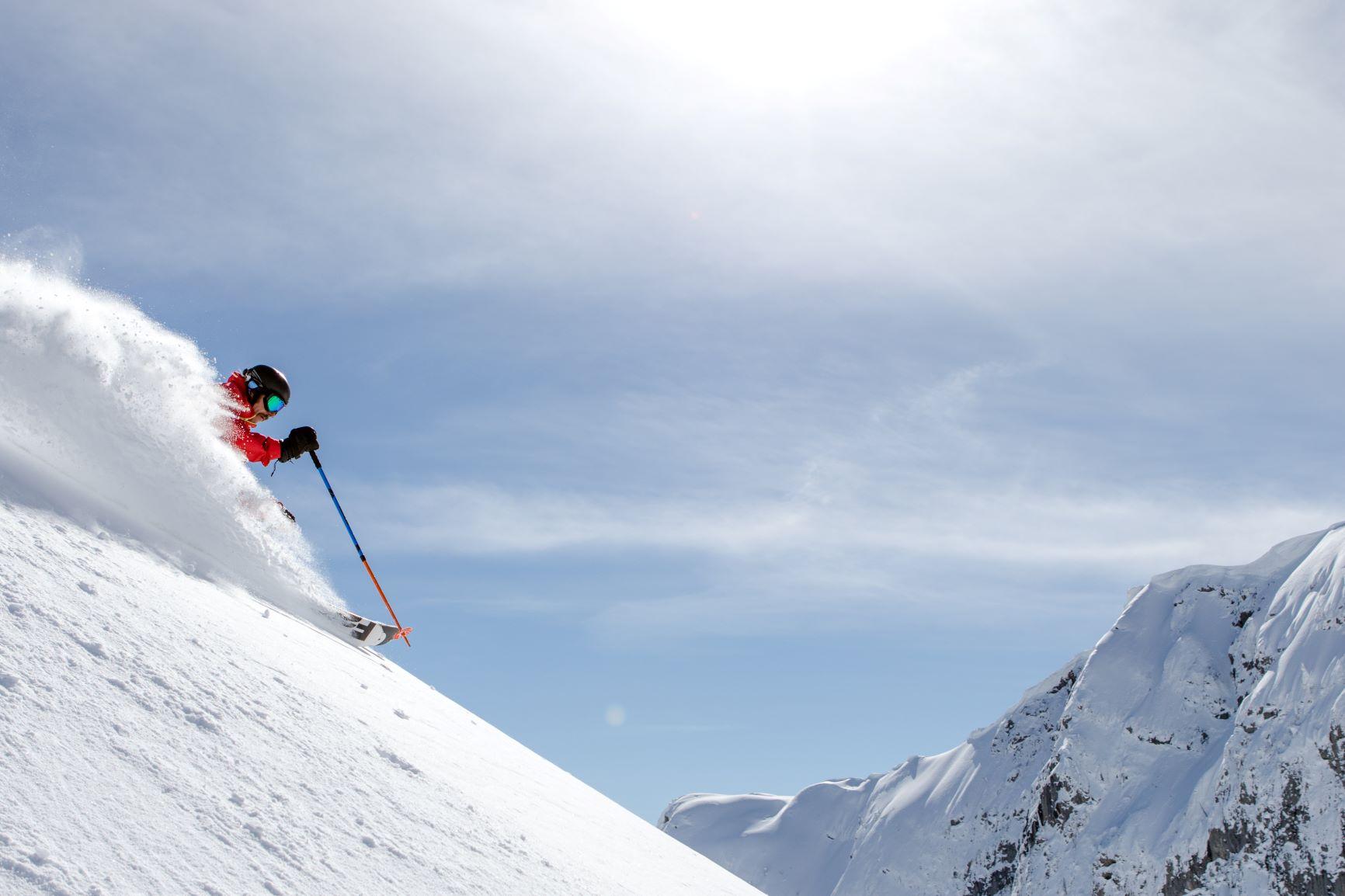 Skier going down a steep and deep powder run