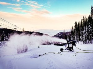 Snow-blowing machine shooting out new snow on a ski run.