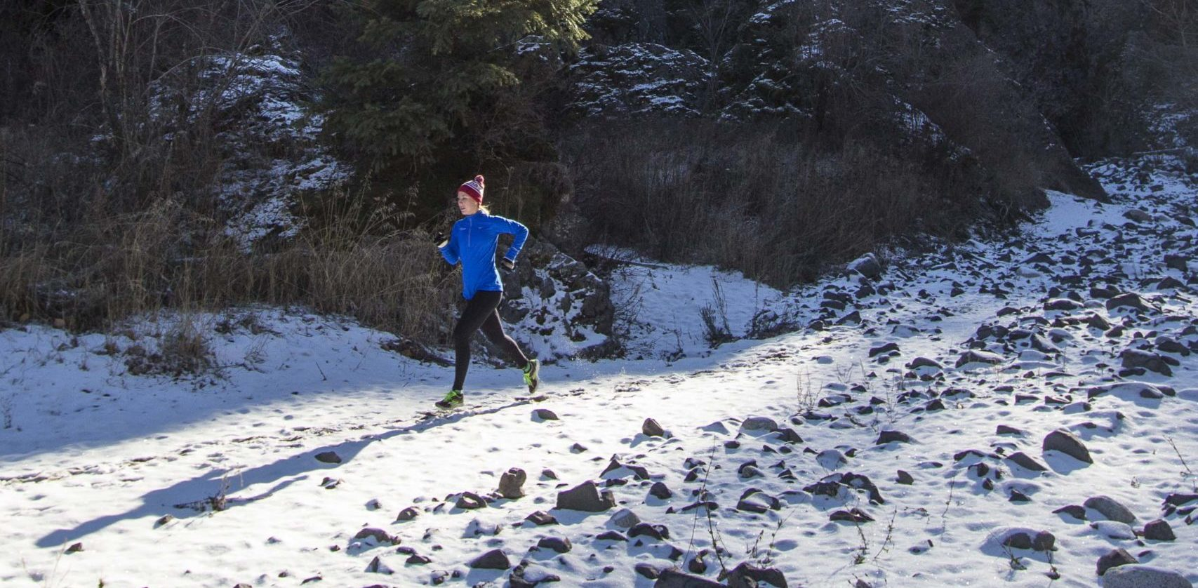 A person running though snowy rocks.