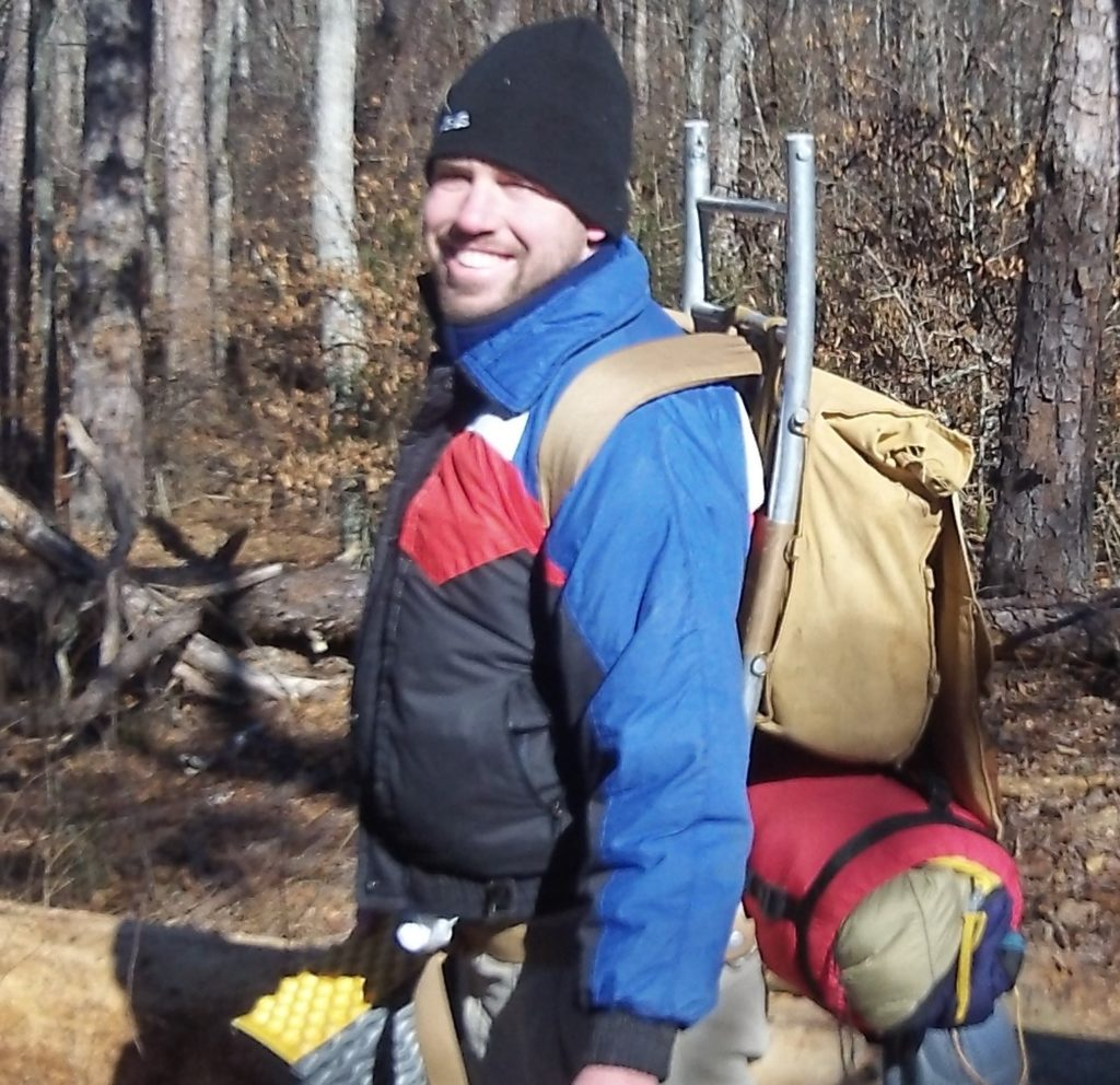 A man smiling with his hiking and camping equipment.