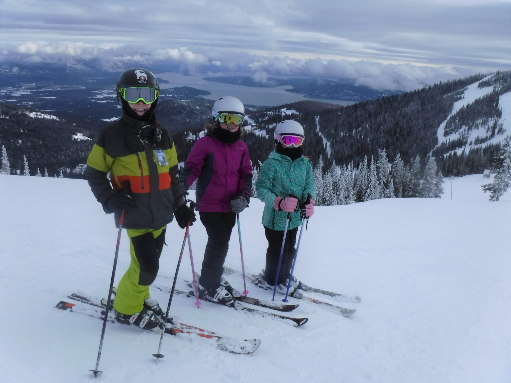 A group of kid skiers on top of a mountain.