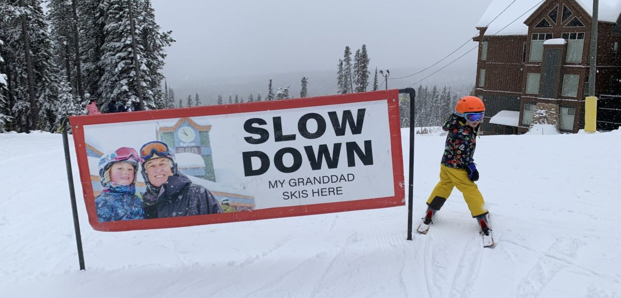 A kid next to a ski sign.