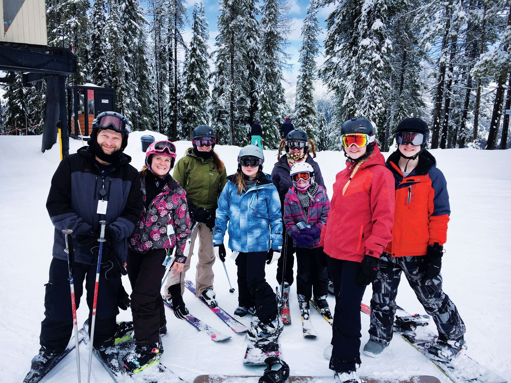 A family group skiing and snowboarding.