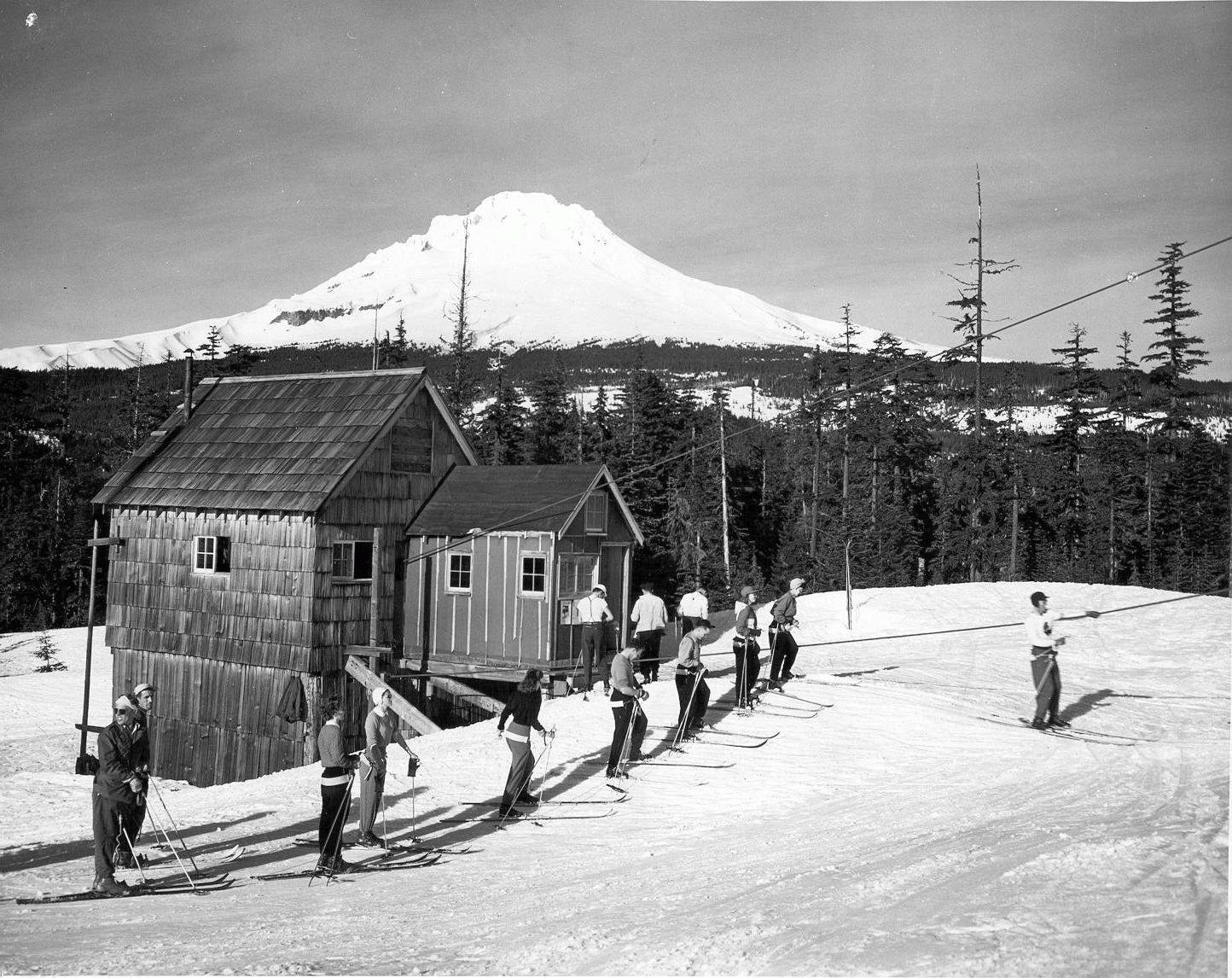 A old black and white vintage photo of people skiing.