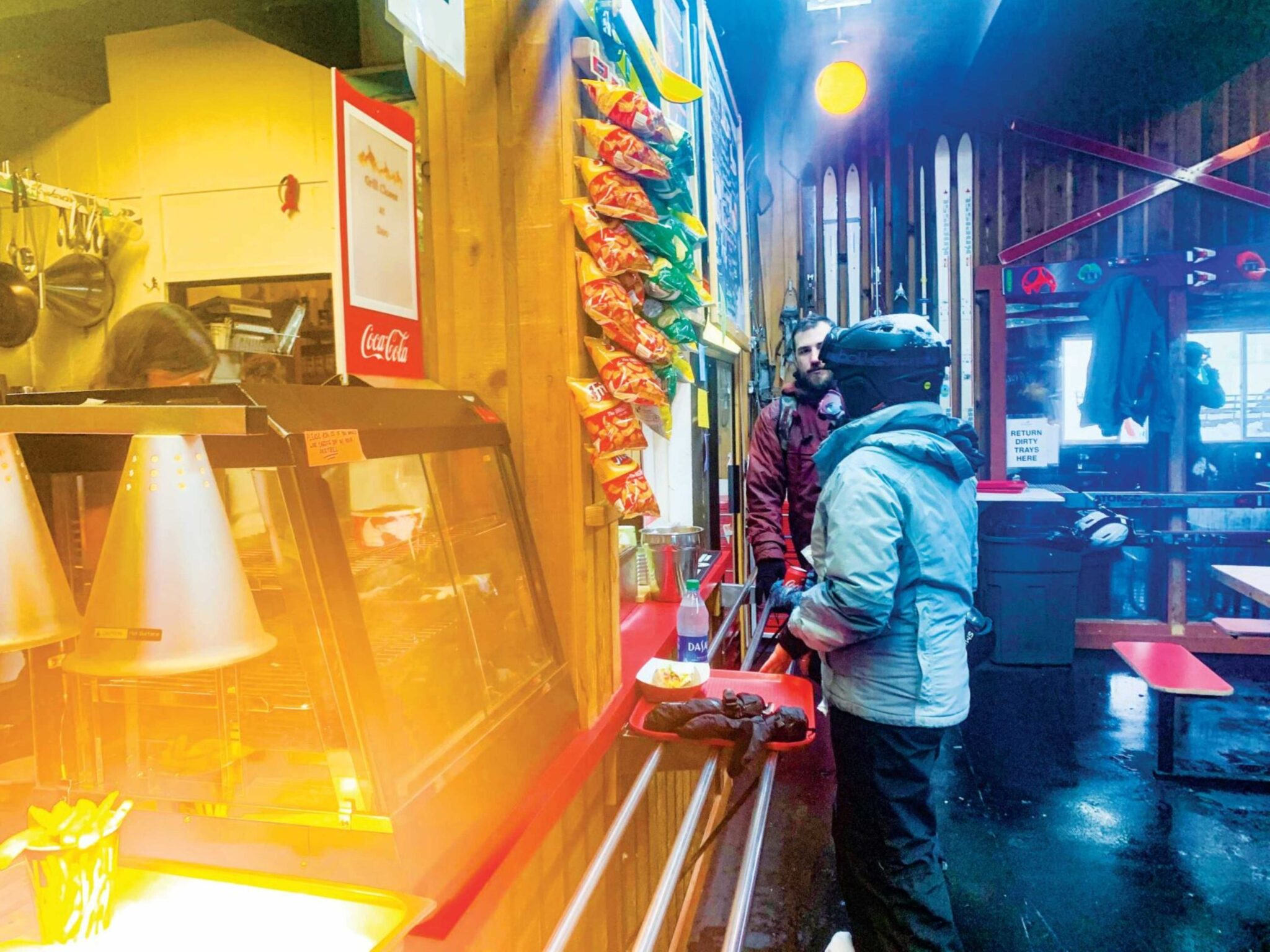 Snowboarder ordering food after snow-boarding.