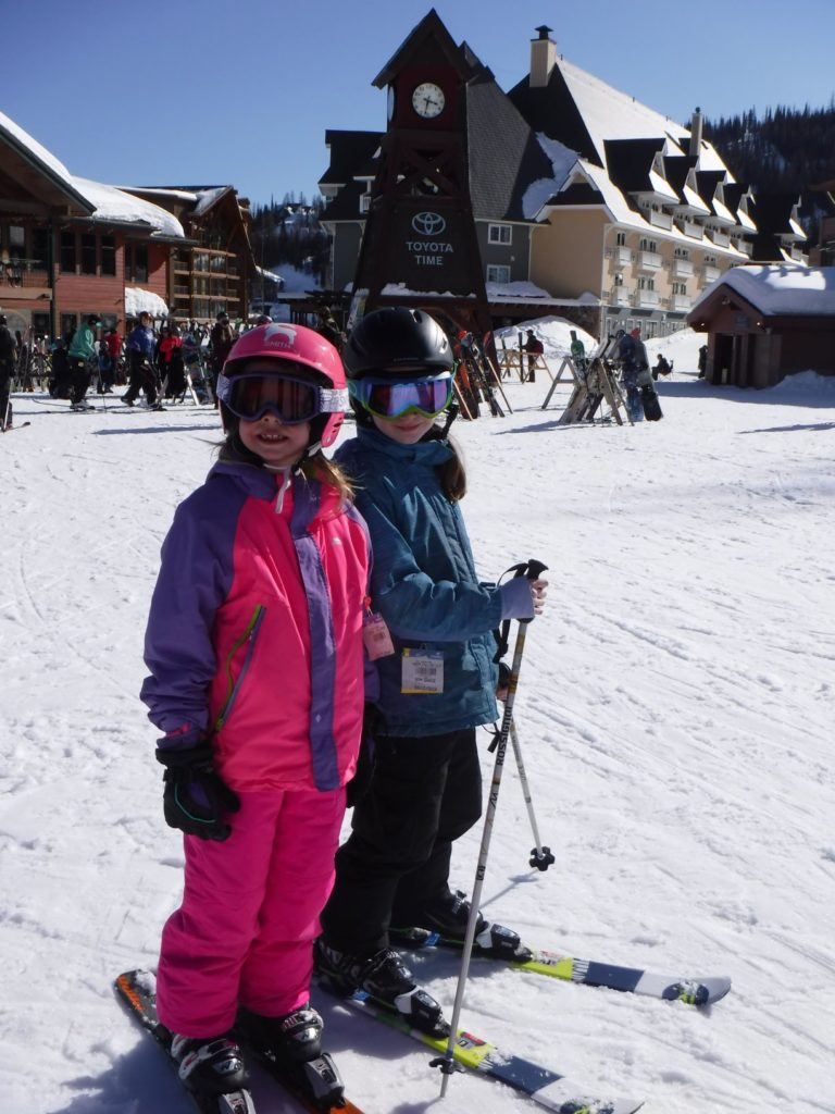 Young skiers in Schweitzer Village, with the clock tower in the background.