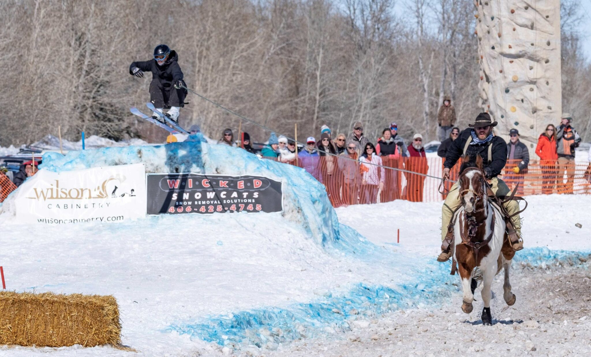 Skier being pulled by a horse while they go off a jump/